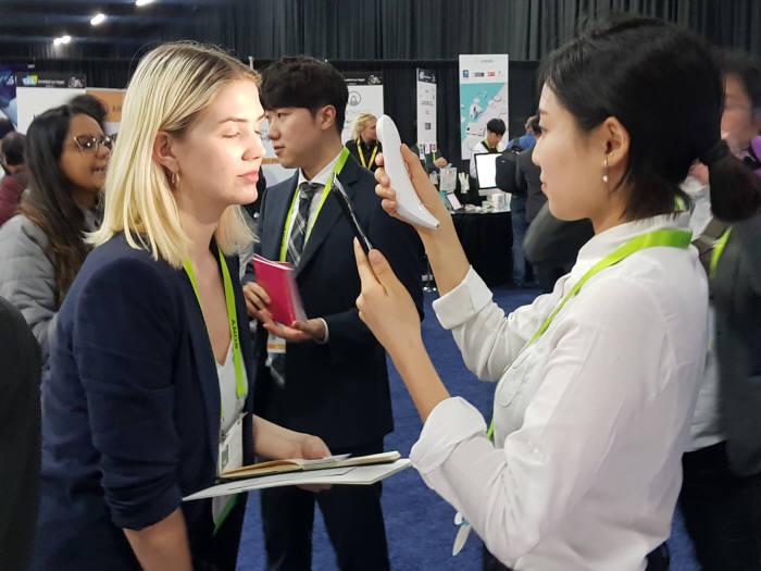 룰루랩 관계자가 CES2019 행사장에서 참관객을 대상으로 피부 상태를 분석하고 있다.