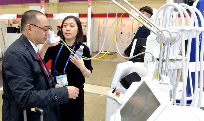 지난해 열린 KIMES2018에서 관람객이 국내기업이 개발한 원격 협진시스템을 살펴보고 있다.(자료: 전자신문DB)