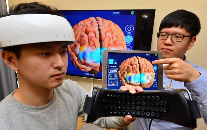 오비이랩 연구진이 초소형 뇌영상 촬영장치를 시연하고 있다.(자료: 전자신문)