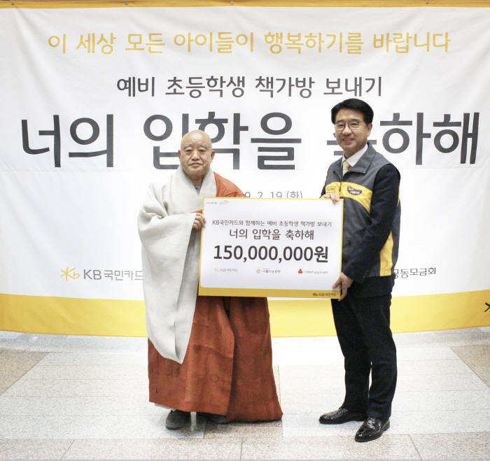 이동철 KB국민카드 사장(오른쪽)이 재단법인 아름다운 동행 이사장인 원행 스님에게 1억5000만원 상당 책가방 선물 세트를 전달하고 있다.
