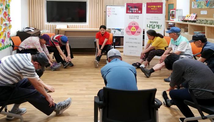 광명보건소 치매안심센터에 국제시니어케어협회 전문트레이너가 어르신들을 대상으로 몸 풀기 체조를 하는 모습.