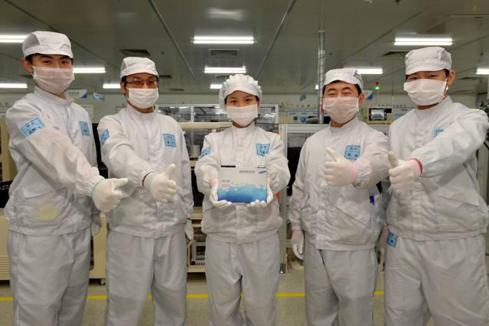 삼성SDI 시안공장 직원들이 생산된 전기차용 배터리를 들어보이고 있다. <삼성SDI 제공>