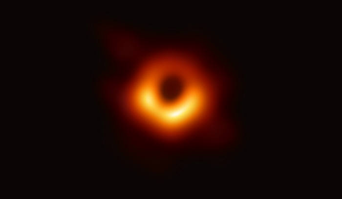 이번에 관측한 M87 중심 이미지. 가운데 검은 부분이 블랙홀(사건의 지평선)과 블랙홀을 포함하는 그림자. 고리의 빛나는 부분은 블랙홀의 중력에 의해 휘어진 빛이다 고리의 아래부분은 빛의 방향이 관측자로 향하고 있어 더 밝게 보인다.