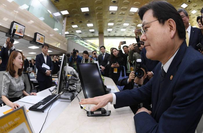 정맥인증으로 간편하게 돈 찾자 최종구 금융위원장이 12일 서울 여의도 KB국민은행 본점에서 정맥인증 서비스 시연을 하고 있다. KB국민은행은 국내 은행 최초로 정맥인증 서비스를 도입한다. 이동근기자 foto@etnews.com