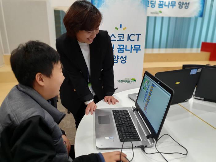 포스코ICT 직원이 코딩 꿈나무 교실에 참여한 청소년에게 스크래치 코딩을 설명하고 있다.