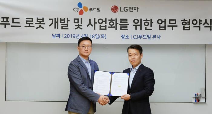 LG전자와 CJ푸드빌이 18일 CJ푸드빌 본사에서 푸드 로봇 공동 개발을 위한 업무협약을 맺었다. 오광석 CJ푸드빌 전략기획담당 헤드(왼쪽)와 노진서 LG전자 로봇사업센터장 전무가 악수하고 있다.