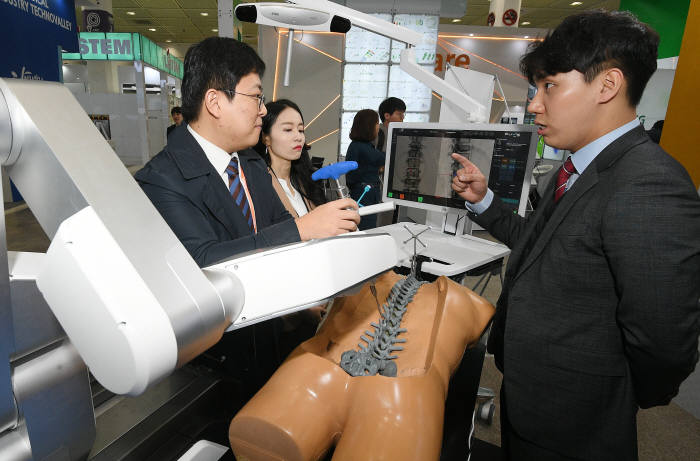 3월 열린 국제의료기기&병원설비전시회에서 참관객이 척추수술로봇 기능을 설명 듣고 있다.(자료: 전자신문 DB)
