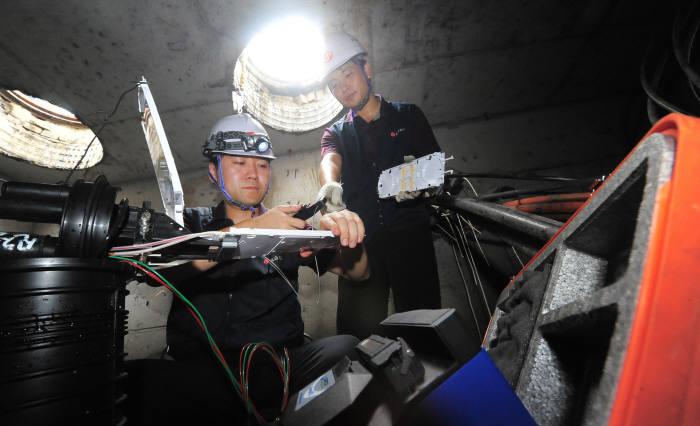 통신사 직원이 맨홀 내 지하통신시설을 점검하고 있다.