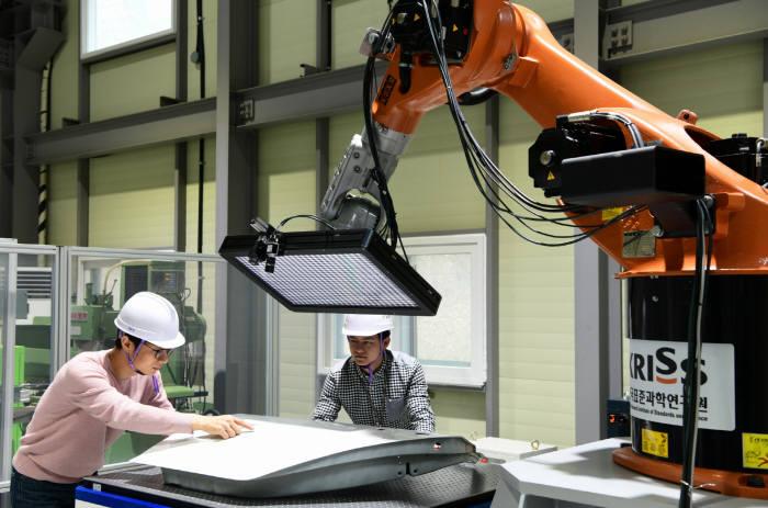 자유곡면 3차원 측정기술 모듈을 탑재한 로봇팔로 스마트폰 커버 글라스 표면을 측정하는 모습