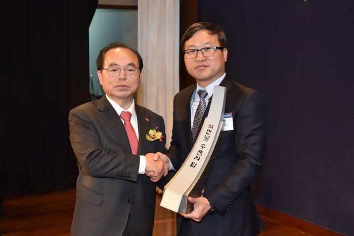 박성백 코노텍 대표(오른쪽)가 오거돈 부산시장으로부터 100만불 수출탑 트로피를 받고 기념촬영했다.