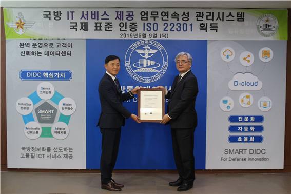 신삼범 국방통합데이터센터장(왼쪽)이 인증기관인 이창섭 DNV GL대표에게 업무연속성관리 국제인증 ISO 22301 인증서를 수여받고 있