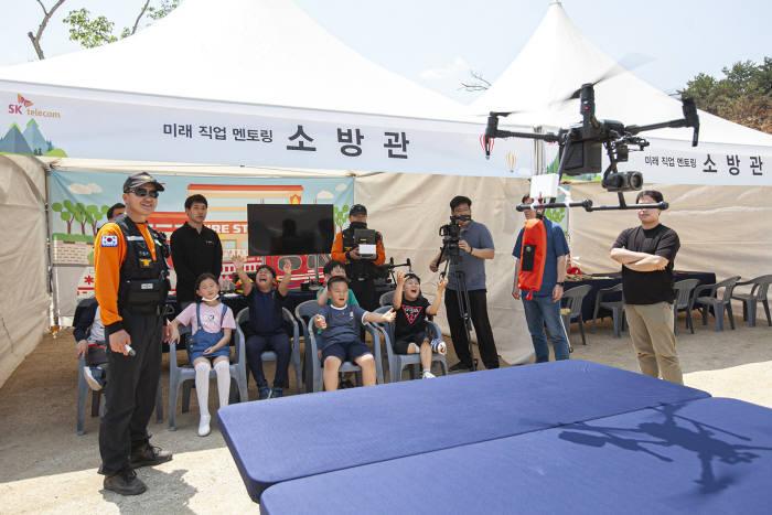 강원소방본부 소속 소방관이 인흥초등학교 학생에게 직업 멘토링을 제공하며 소방 드론을 시연하고 있는 모습.