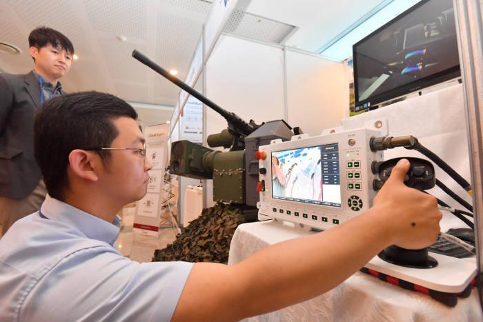 현대 위아 부스에서 연구원이 외부 원격사격통제시스템을 내부 사격통제장치로 조종해 사격하는 모습을 시연하고 있다. 박지호기자 jihopress@etnews.com