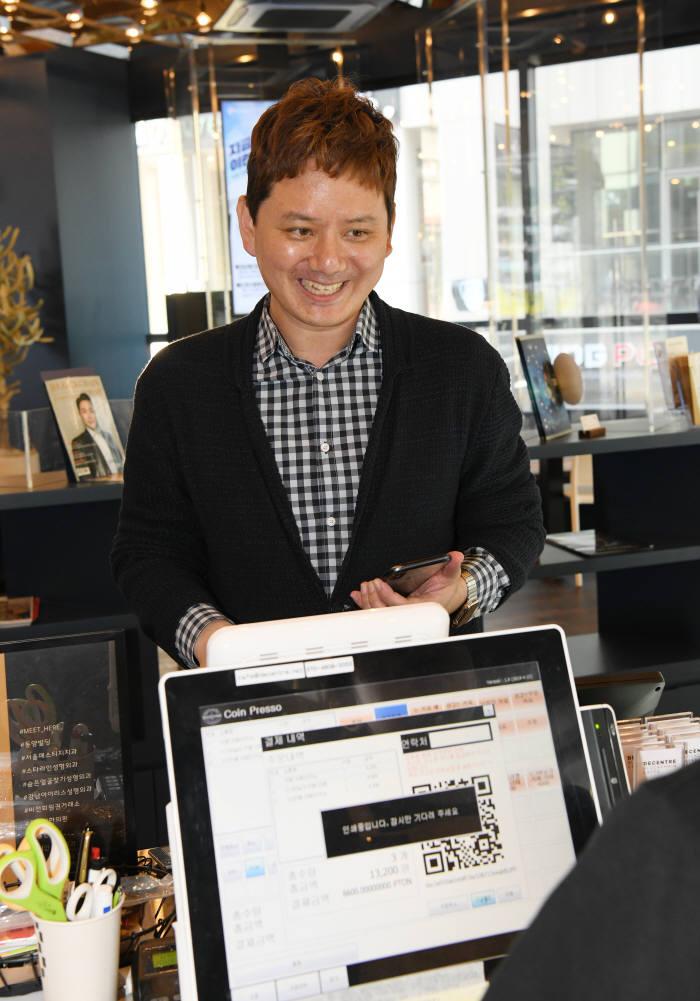 이동혁 디센트레 대표가 서울 강남구 신논현역에 위치한 디센트레 카페에서 전자지갑을 열어 가상화폐로 커피 값을 결제하고 있다.