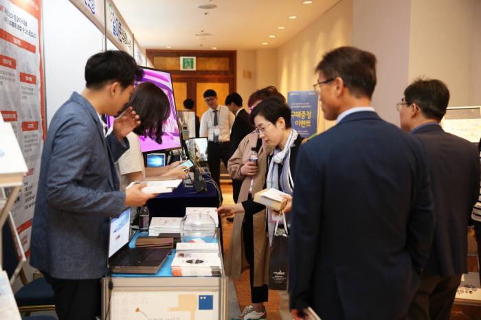 제17차 한국학술정보협의회 정기총회 및 콘퍼런스 참가자들이 미래도서관 서비스 관련 전시부스를 둘러보고 있다