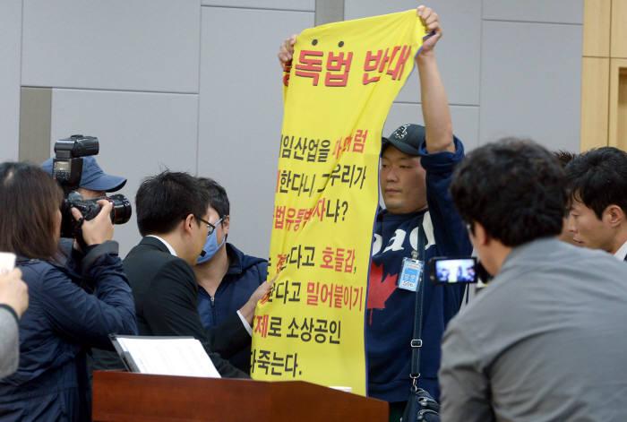 4대 중독예방관리제도 마련 공청회가 2013년 서울 여의도 국회의원회관에서 열렸다. 토론 진행 중 한 참석자가 중독법 반대 플래카드를 펼치려하자 관계자들이 제지하고 있다. 박지호기자 jihopress@etnews.com