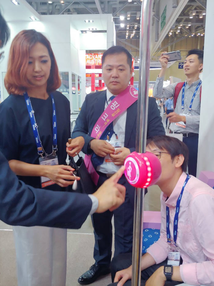 부산국제철도기술산업전 핑크라이트 부스에서 관람객들이 핑크라이트 임산부 배려석 알림 기능을 체험하고 있다.