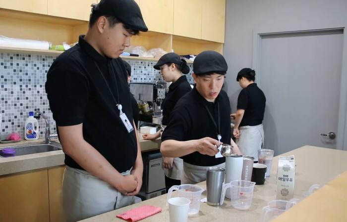 SK이노베이션의 자회사형 장애인 표준사업장 행복키움이 운영하는 카페 행복에서 장애인 근로자들이 바리스타 교육을 받고 있다. (사진=SK이노베이션)