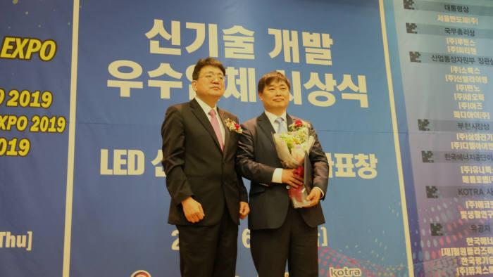 유현종 서울반도체 대표이사(오른쪽)가 대통령상을 수상하고 상패를 들고 있다.