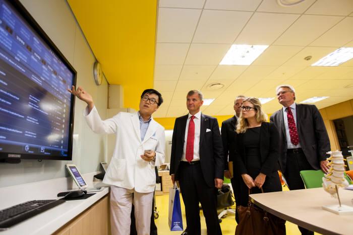 분당서울대병원 의료진이 병원을 방문한 해외 관계자에게 병원정보시스템(HIS) 베스트케어 2.0으로 구현되는 기능을 설명하고 있다.