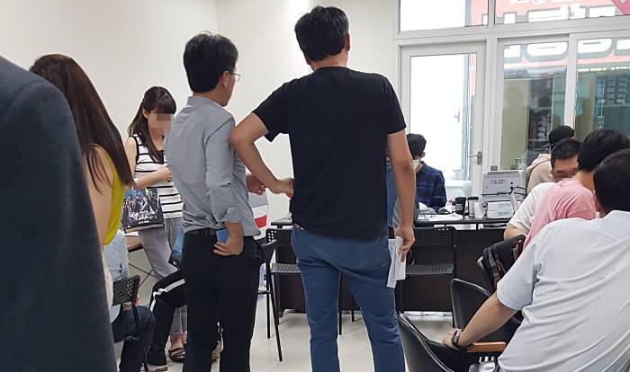 강서 지역의 성지라 불리는 스팟성 휴대폰 판매점. 5~6평 정도 작은 공간, 10여명이 간이 의자에 앉고 서서 대기하던 줄은 퇴근 시간이 지나자 금세 복도 밖까지 20~30여명이 늘어섰다.