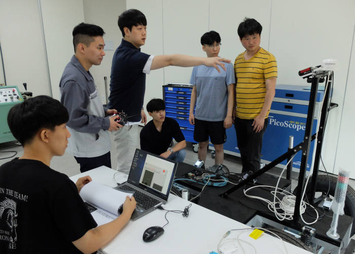 신동준 한국폴리텍대학 화성캠퍼스 스마트자동차학과장(왼쪽 세번째)이 교육생에게 자율주행차 기술을 설명하고 있다.