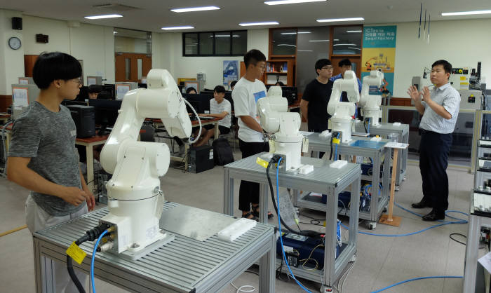 김정현 한국폴리텍대학 창원캠퍼스 스마트팩토리과 교수(맨 오른쪽)가 교육생들에게 공작 로봇 제어방법을 설명하고 있다.