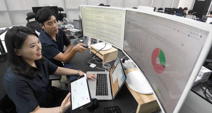 삼성전자 출신이 모여 설립한 스타트업 포지큐브가 국내 최초 상점형 AI 서비스를 상용화하는데 성공했다. 주말 서울 서초구 포지큐브 개발자가 배달, 주문 예약 등이 가능한 인공지능 로비 서비스 시스템에 대해 논의하고 있다. 김동욱기자 gphoto@etnews.com