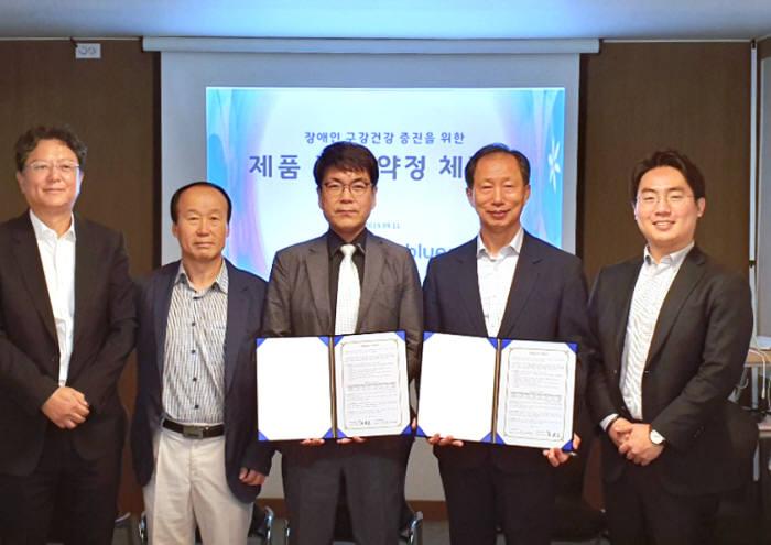 이우재 블루레오 전무(왼쪽 세 번째)가 일과복지 관계자(〃 네 번째)와 장애인 구강건강을 위한 보조기기 지원사업 제품공급 약정서를 교환하고 있다.