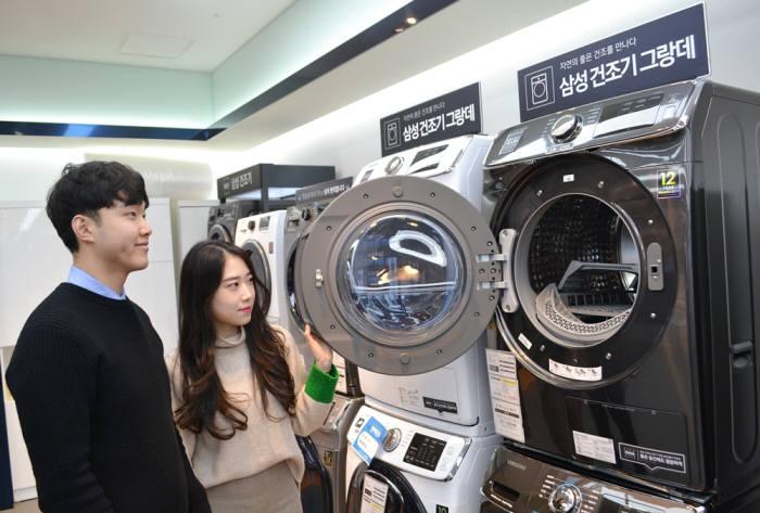 가전양판점에서 소비자들이 건조기를 살펴보고 있다.
