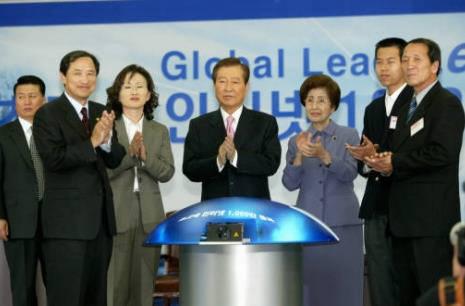 김대중 대통령이 초고속 인터넷 1000만 돌파 기념식에서 1000만 돌파를 알리는 3X3 멀티큐브 대형마우스를 누른 뒤 박수치고 있다.