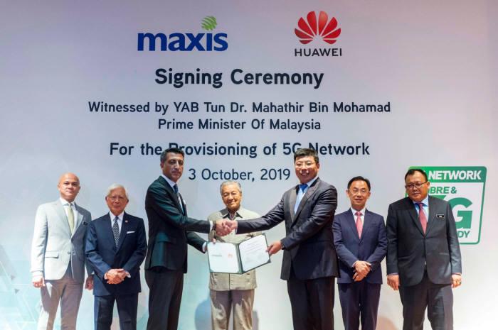 고칸 우트(Gokhan Ogut) 맥시스 최고경영자(CEO, 왼쪽)와 마이클 위안(Michael Yuan) 화웨이 말레이시아 최고경영자(CEO)가 5G 네트워크 구축 협약을 체결했다. 뒷줄 가운데는 마하티르 모하맛(Mahathir bin Mohamad) 말레이시아 총리