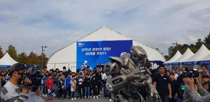 18일 대전 엑스포시민광장에서 열린 대전사이언스페스티벌에 참여한 시민들이 로봇 타이탄을 구경하고 있다.