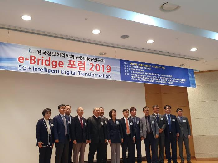 한국정보처리학회 e-브리지 연구회(회장 이정배·부산외대 부총장)는 30일 대전 ETRI 융합기술연구센터에서 e-브리지 포럼 2019을 개최했다. 민관이 함께 참여하는 연구회는 미래를 설계하는 일을 추진하기 위해 3년전부터 포럼을 꾸준히 개최하고 있다. 연구회는 올해 5G+ 인텔리전트 디지털트랜스포메이션이란 주제로 포럼을 열었다. 안문석 공동대회장(왼쪽 네 번째)를 비롯한 포럼 관계자들이 기념촬영했다.