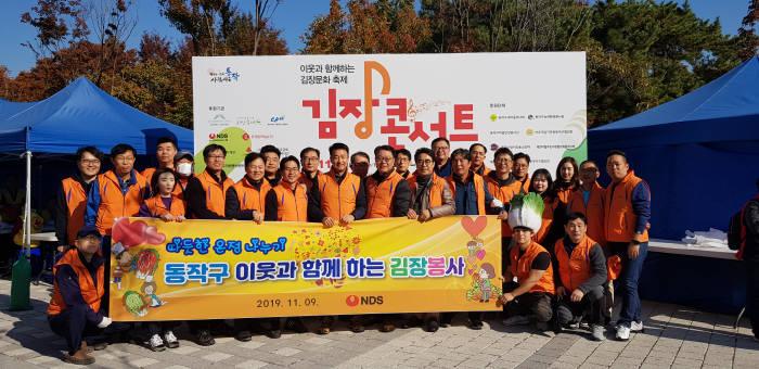 클라우드 기반의 IT서비스 기업 NDS가 동작구 지역 주민의 겨울나기 봉사 활동에 참가하기 위해 이웃과 함께하는 김장문화 축제, 김장콘서트에 동참했다. 이날 김중원 NDS 대표(사진 앞줄 왼쪽 6번째)를 포함한 임직원들은 정직과 성실한 자세로 맡은 일에 최선을 다하는 기업으로서 지역 사회 발전에 기여하자고 재다짐했다.