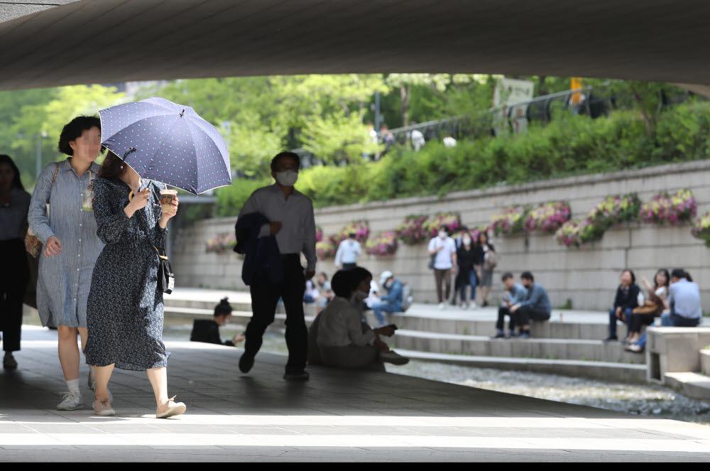 서울 낮 최고 기온이 26도를 기록한 4일 오후 서울 청계천에서 양산을 든 시민이 걸어가고 있다. <연합뉴스>