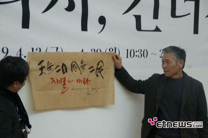 11일 서울 종로구 세종문화회관 세종미술관에서는 정태춘·박은옥 40주년 기념 트리뷰트 전시회 '다시, 건너간다' 기자간담회가 개최됐다. 새롭게 쓴 붓글을 선보이는 정태춘.