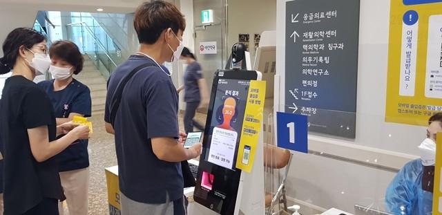 한 내원객이 서울의료원에 설치된 포씨게이트의 CSTS(비접촉 안면온도 측정시스템)을 사용해보고 있다.