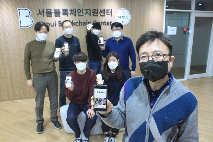 지난 15일 서울 마포구 서울블록체인지원센터에 입주한 블록펫 직원들이 반려동물 SNS 플랫폼 '펫컴퍼니'를 들어보이며 포즈를 취하고 있다. 사진 맨 앞은 박희근 블록펫 대표