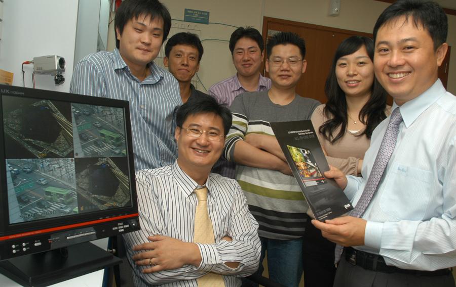 유홍식 대표(앞줄 왼쪽)와 직원들이 새로 출시된 LCD모니터 일체형 DVR 앞에서 환하게 웃고 있다.