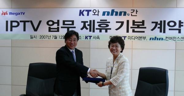 NHN 윤대균 컨버전스 센터장(좌)과 KT 이영희 미디어본부장이 계약서를 교환하고 악수를 나누고 있다.