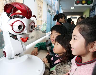 R러닝이 첨단기술을 기반으로 학교 교육의 질을 바꿔놓고 있다. 지난해 12월 경남 마산 합포초등학교 학생들이 영어교사보조로봇인 메로의 입술 모양을 살펴보며 영어 발음을 따라하고 있다.