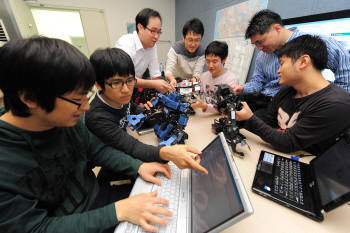 광운대 정보제어학과 교수와 학생들이 휴머노이드 로봇의 움직임과 프로그래밍에 관해 의견을 나누고 있다.