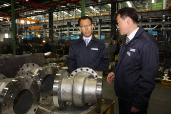 김태만 엔에스브이 대표(왼쪽)가 임원과 함께 밸브  생산공정을 살펴보고 있다