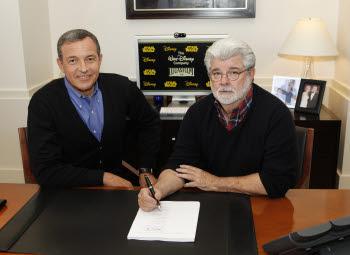 밥 아이거 디즈니 CEO(왼쪽)와 조지 루카스 루카스필름 회장이 30일(현지시각) 계약서에 싸인하고 있다. <버뱅크(미국)=로이터연합뉴스>