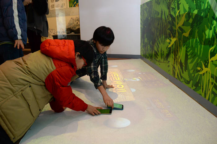 ETRI가 개발한 `도슨트` 기술이 `천연기념물센터`에 설치돼 시범운영 중이다. 천연기념물센터를 찾은 어린이들이 스마트폰을 통해 `공룡알을 옮겨라`라는 놀이를 체험하고 있다.