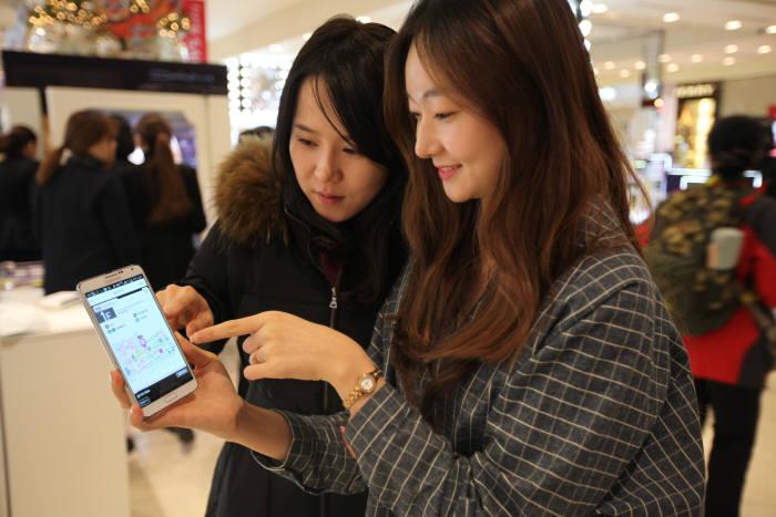 롯데백화점을 찾은 소비자가 비콘을 통해 스마트폰에 자동으로 알려주는 할인 정보를 확인하고 있다.
