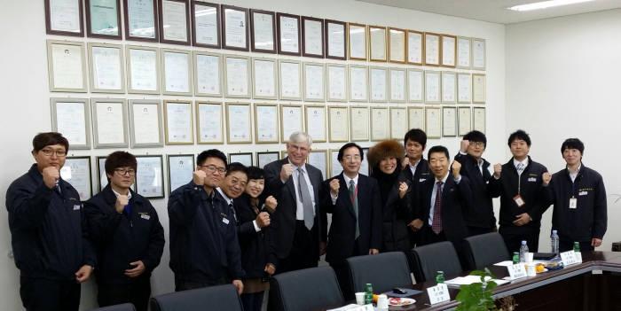 박종복 케이에스비 대표(왼쪽 일곱 번째)와 임직원이 회사를 방문한 미국 고객과 파이팅을 외치고 있다. 벽면에 이 회사가 받은 특허가 걸려있다.