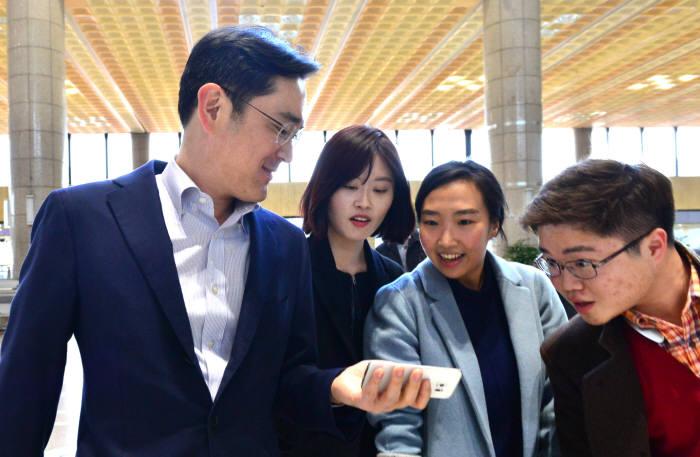 보아오포럼 참석차 24일 중국으로 출국한 이재용 삼성전자 부회장이 서울 김포국제공항에서 기자들에게 자신의 `갤럭시S6 엣지`를 보여주며 이야기를 나누고 있다. / 윤성혁기자 shyoon@etnews.com