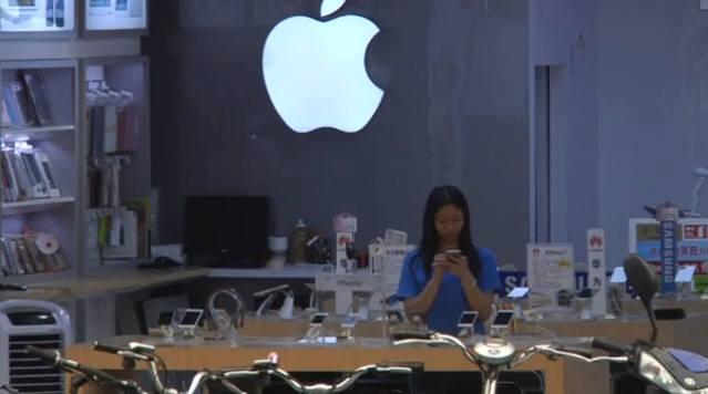 중국 선전시에 등장한 가짜 애플 매장 전경. 점원이 공식 애플스토어 직원과 같은 파란색 티셔츠를 입고 애플로고 앞에 서있다.